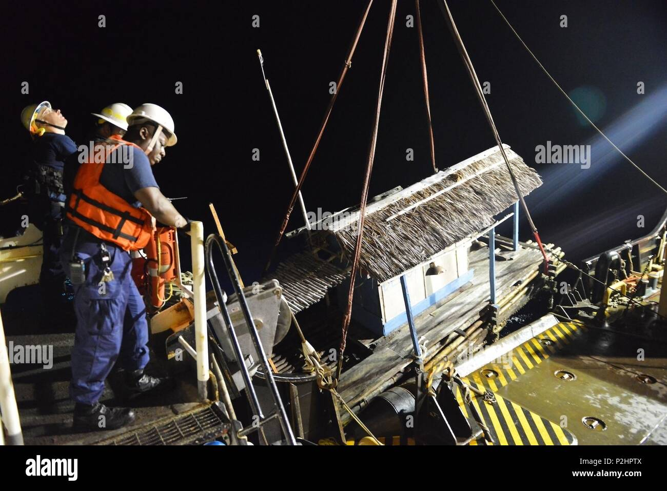 U.S. Coast Guard Senior Chief Petty Officer Mark Petty, a boatswain's mate, checks the crane as the crew of the buoy tender USCGC Sequoia (WLB-215) recovers an illegal fish aggregating device located in the Palau exclusive economic zone that presented a hazard to navigation Sept. 3, 2016. Fishermen use well lit FADs to attract fish to one spot to catch, a practice which is illegal in the Palau EEZ. (U.S. Coast Guard photo by Chief Petty Officer Sara Mooers) - Stock Image