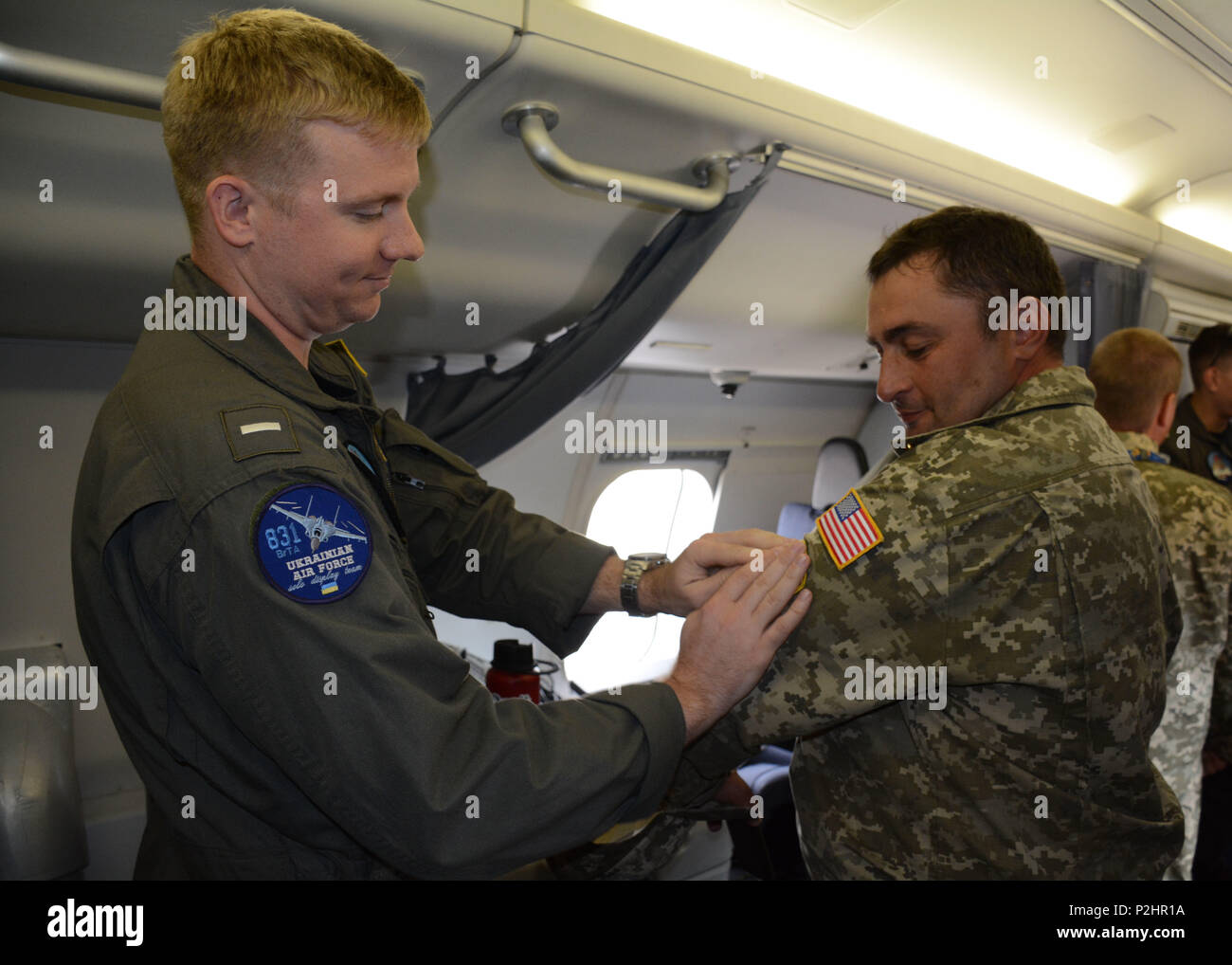 160924-N-HH215-044  LUQA, Malta. (Sept. 24, 2016) Lt. j.g. Tanner Anjola, left, Patrol Squadron (VP) 45 co-tactical coordinator, presents a P-8A Poseidon aircraft patch to Ukrainian Air Force (UAF) Capt. Karabeza Dmytro after receiving a UAF patch during a static display at the 2016 Malta International Airshow, Sept. 24. U.S. 6th Fleet, headquartered in Naples, Italy, conducts the full spectrum of joint and naval operations, often in concert with allied, joint, and interagency partners, in order to advance U.S. national interests and security and stability in Europe and Africa. (U.S. Navy phot Stock Photo