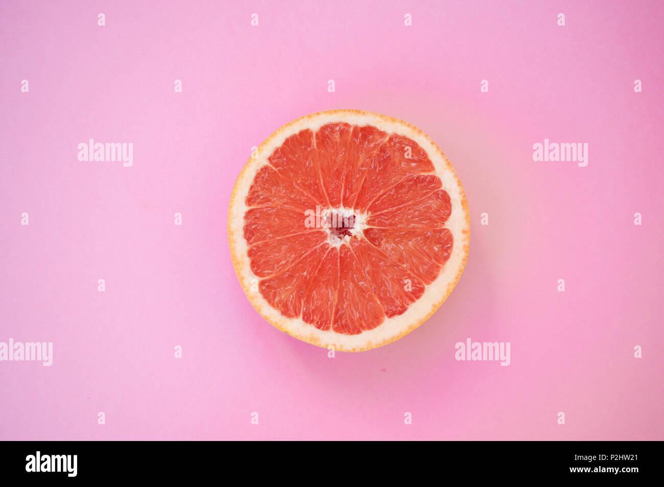 Beautiful juicy cut grapefruit on pastel pink background. Stock Photo