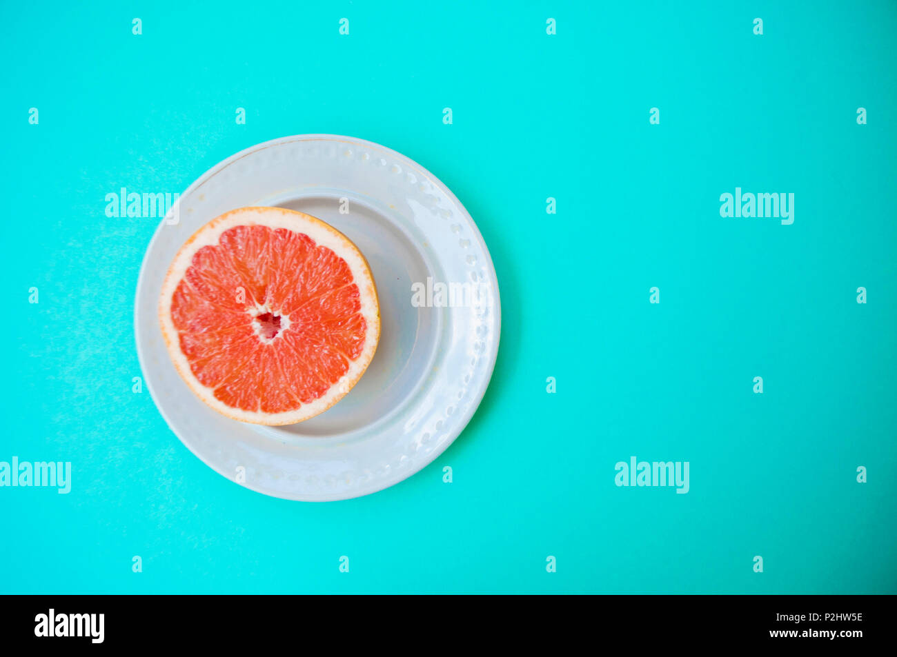 Ripe juicy cut grapefruit on a white plate on blue background with text space. - Stock Image
