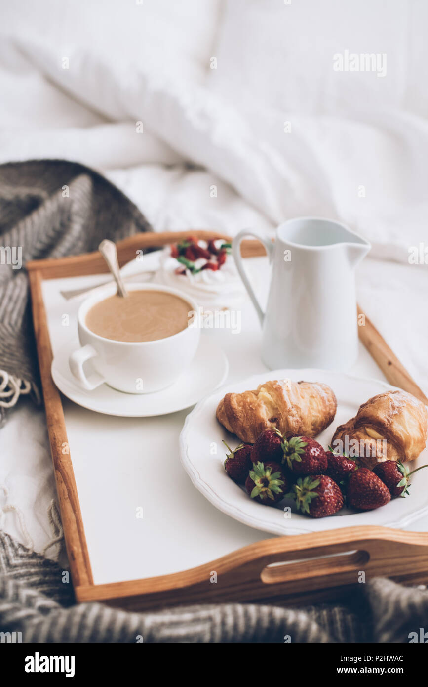 Traditional romantic breakfast in bed in white and beige bedroom ...