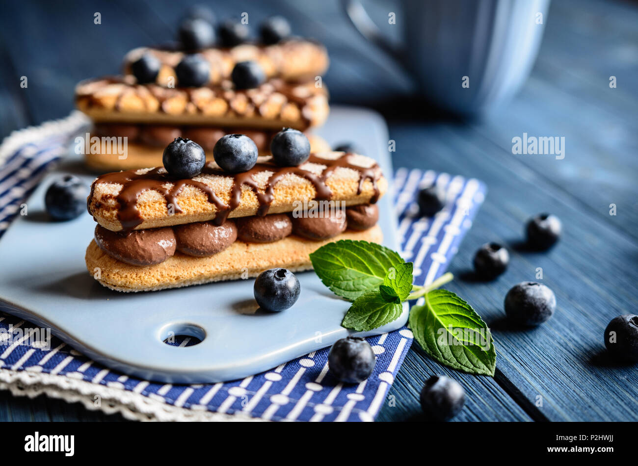 Ladyfingers filled with cocoa mascarpone cream, topped with chocolate and blueberry - Stock Image