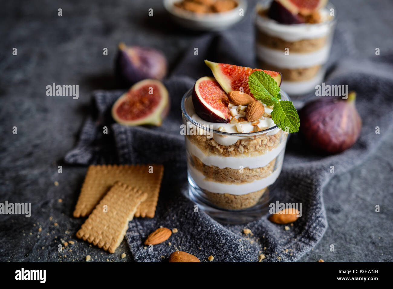 Layered mascarpone dessert with crushed vanilla biscuits, figs and almonds in a glass jar - Stock Image