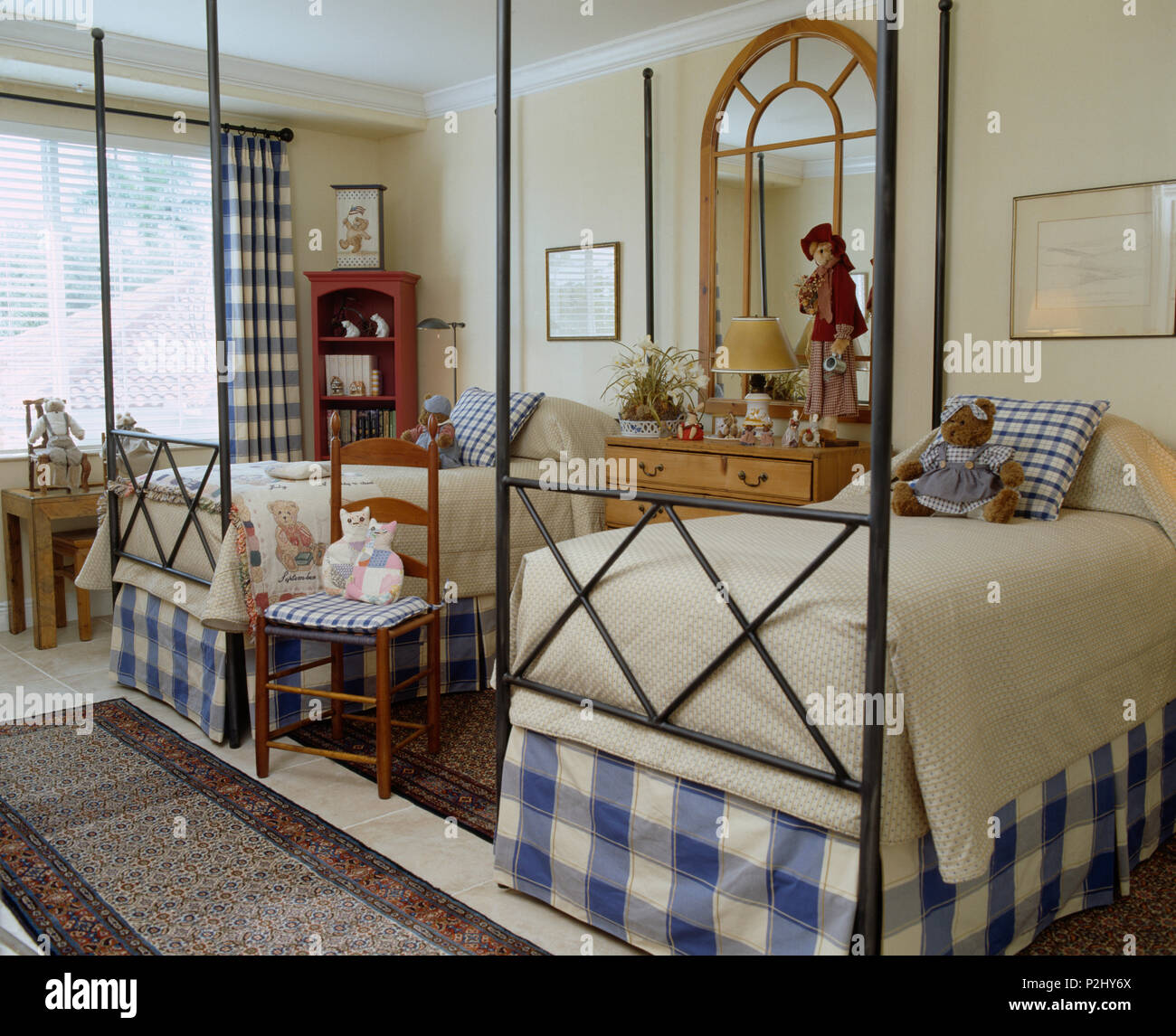 Blue+white checked valences on twin metal-framed beds in light and airy children's coastal bedroom Stock Photo