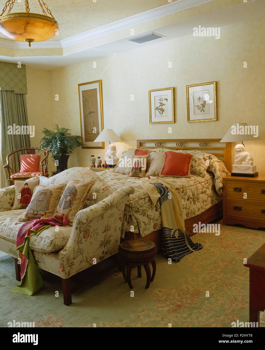 Sofa at foot of bed with quilted bed-cover in a comfortable