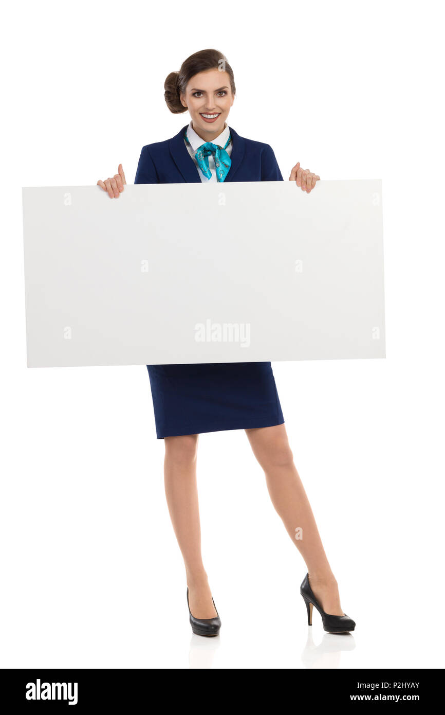 Smiling young woman in blue formalwear and high heels is holding white blank placard. Front view. Full length studio shot isolated on white. - Stock Image