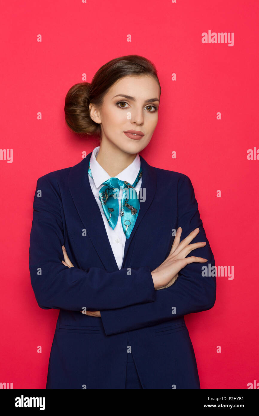 Young woman in blue suit and turquoise scarf posing with arms crossed. Three quarter length studio shot on red background. - Stock Image