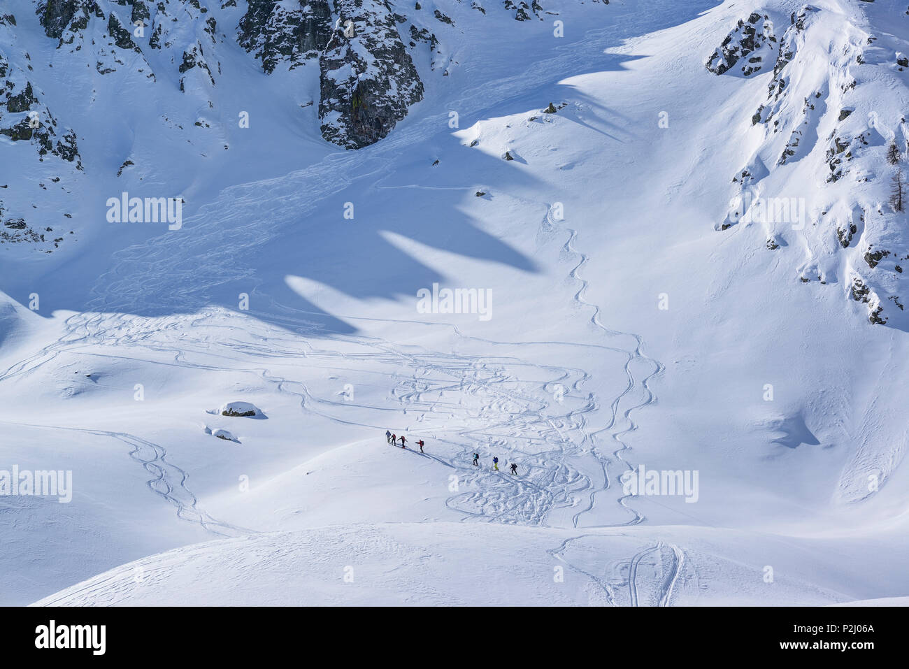 Several persons back-country skiing ascending to Passo Croce, Passo Croce, Valle Maira, Cottian Alps, Piedmont, Italy - Stock Image