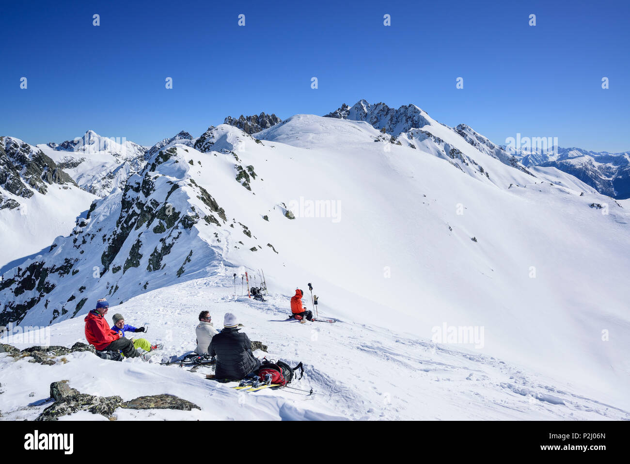 Several persons back-country skiing having a break at Passo Croce, Passo Croce, Valle Maira, Cottian Alps, Piedmont, Italy - Stock Image