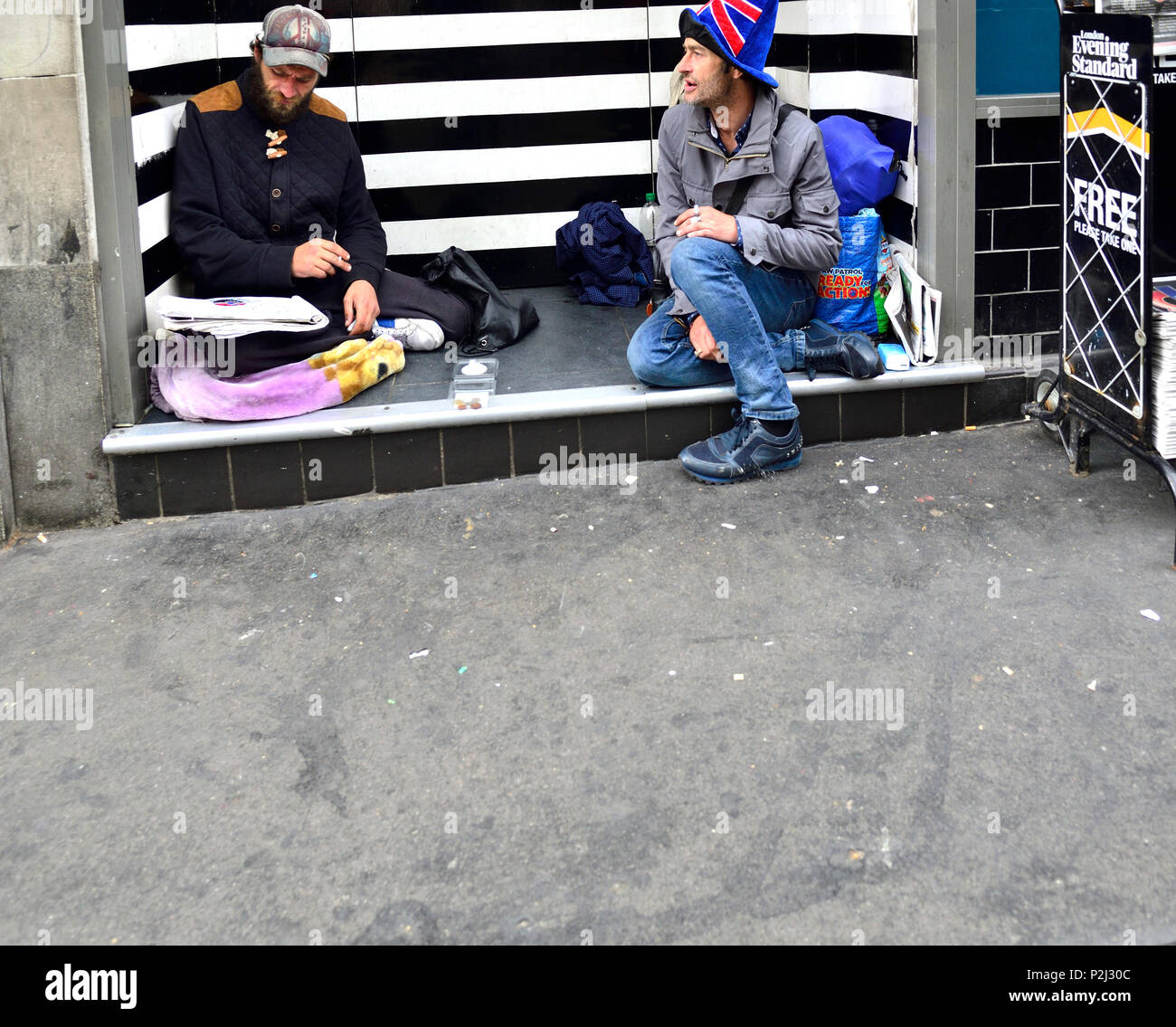 Two homeless men sitting in a doorway, the Strand, London, England, UK. Stock Photo