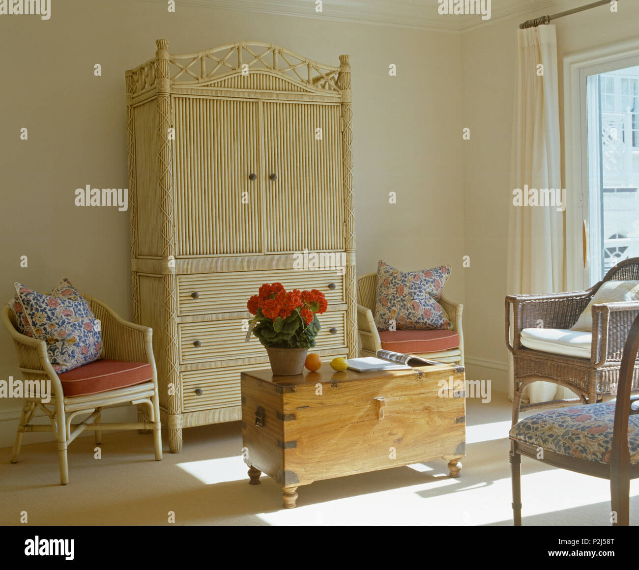 Cream bamboo secretaire cabinet and pine chest in corner of sunlit bedroom with cane armchairs with floral cushions - Stock Image
