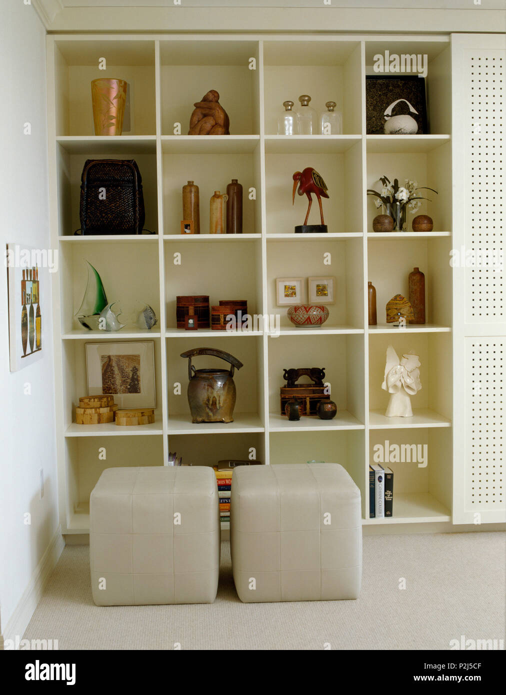 Square beige leather stools in front of cube shelving in ...