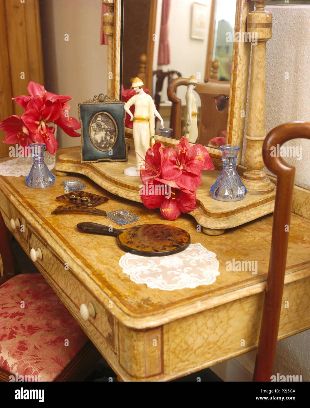 Faux amaryllis on vintage dressing table with tortoiseshell vanity set and thirties figurine - Stock Image