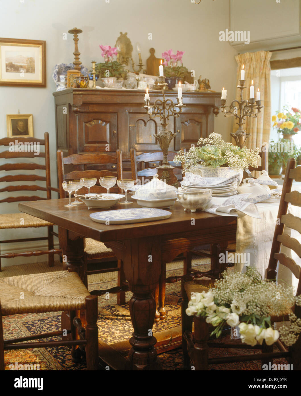 Vintage Ladderback Chairs At Old Oak Table In Country Dining Room Stock Photo Alamy