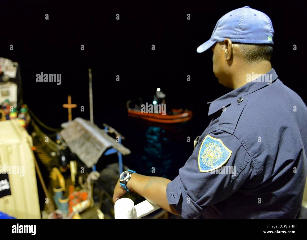 Jim Kloulechad, a Palau National Police officer, observes the crew of the U.S. Coast Guard buoy tender cutter USCGC Sequoia (WLB-215) begin to recover illegal fish aggregating device located in the Palau exclusive economic zone that presented a hazard to navigation Sept. 3, 2016. Fishermen use well lit FADs to attract fish to one spot to catch, a practice which is illegal in the Palau EEZ. (U.S. Coast Guard photo by Chief Petty Officer Sara Mooers) - Stock Image