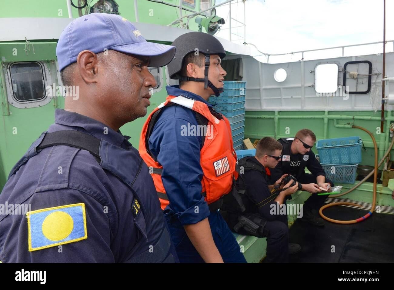 U.s. coast Guard Seaman Neal Vincent Edera, a food service specialist and Tagalog speaker, and Jim Kloulechad, a Palau National Police officer, converse with the crew of the vessel as other members of the boarding team review the fishermen's passports and identification aboard the fishing vessel Ayamaru No. 58 while underway in the Palau exclusive economic zone Sept. 3, 2016. The Coast Guard, working with the Palau National Police conducted fisheries enforcement boardings in the Palau EEZ under a bilateral agreement. (U.S. Coast Guard photo by Chief Petty Officer Sara Mooers) - Stock Image