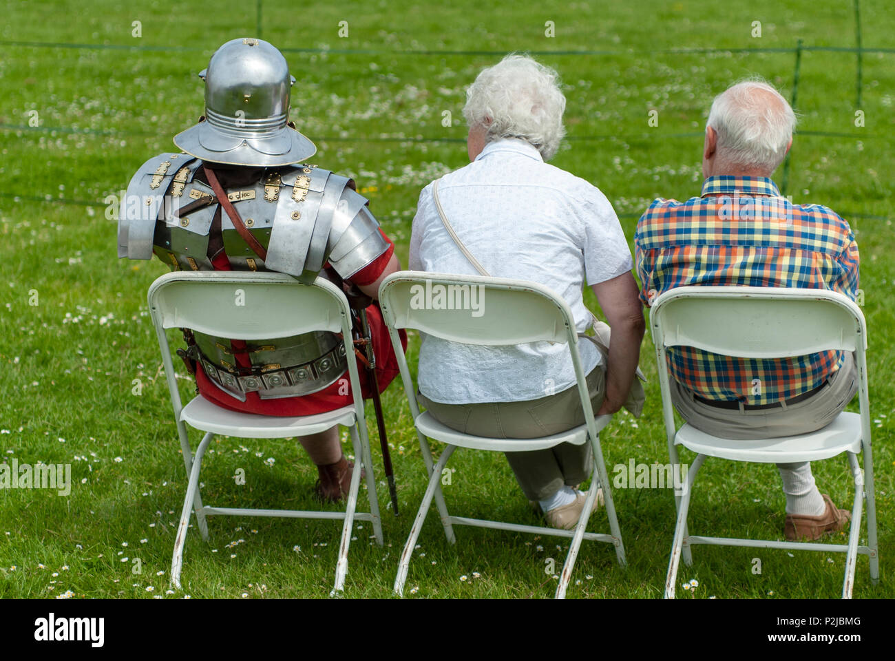 Romans in Britain!  XX Legion Re-enactment solider takes a rest with his parents!  Living history group at Portchester Castle, Hampshire, UK - Stock Image