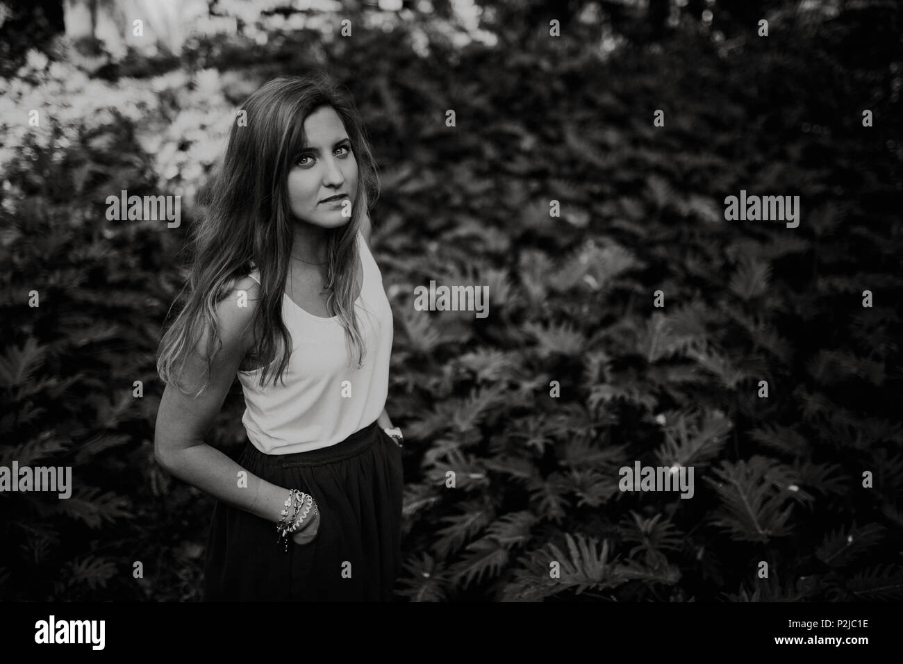 Black and white portrait of young blonde woman standing between plants in the forest