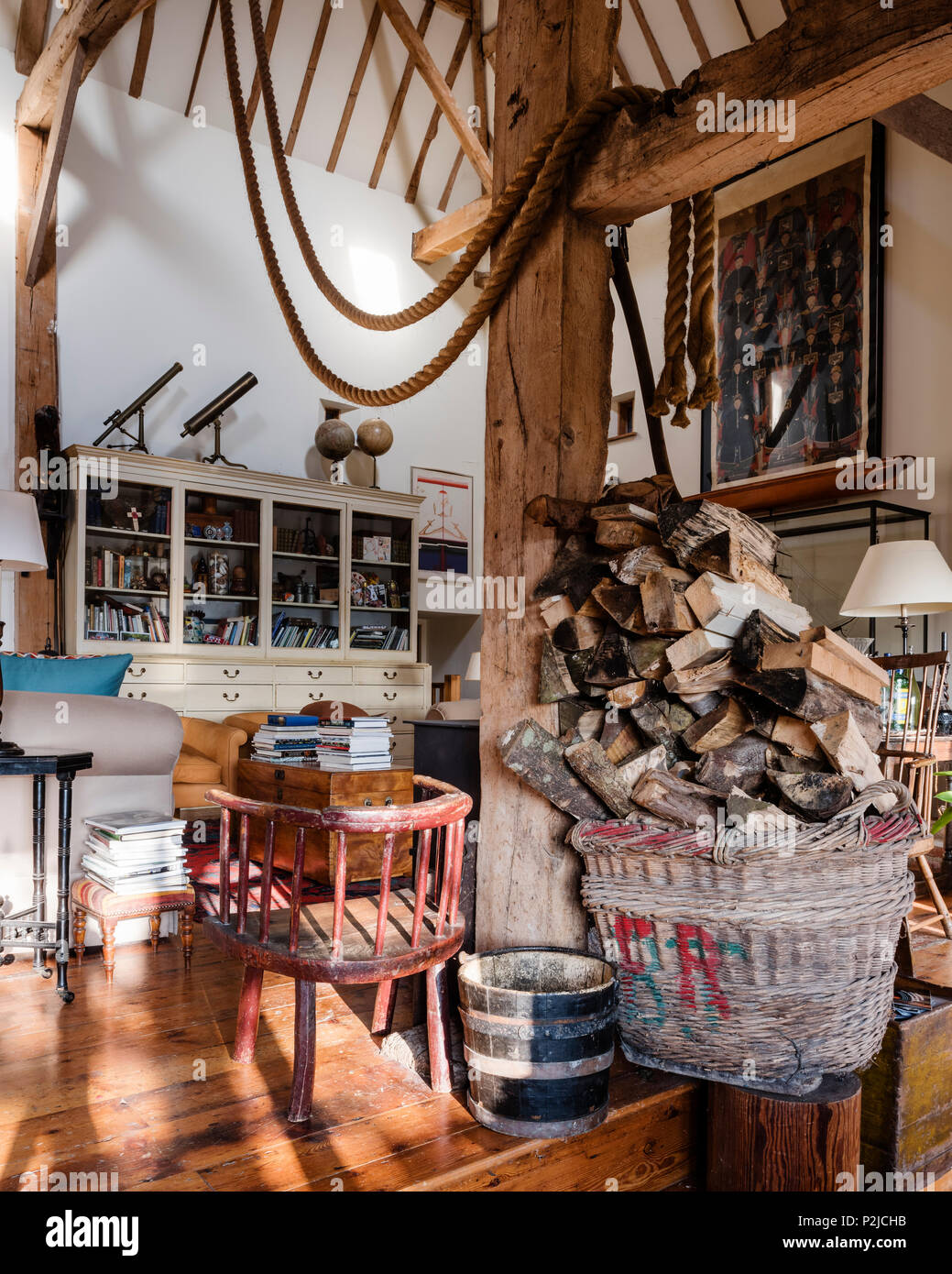 Ship ropes with firewood in log basket in Sussex barn conversion - Stock Image