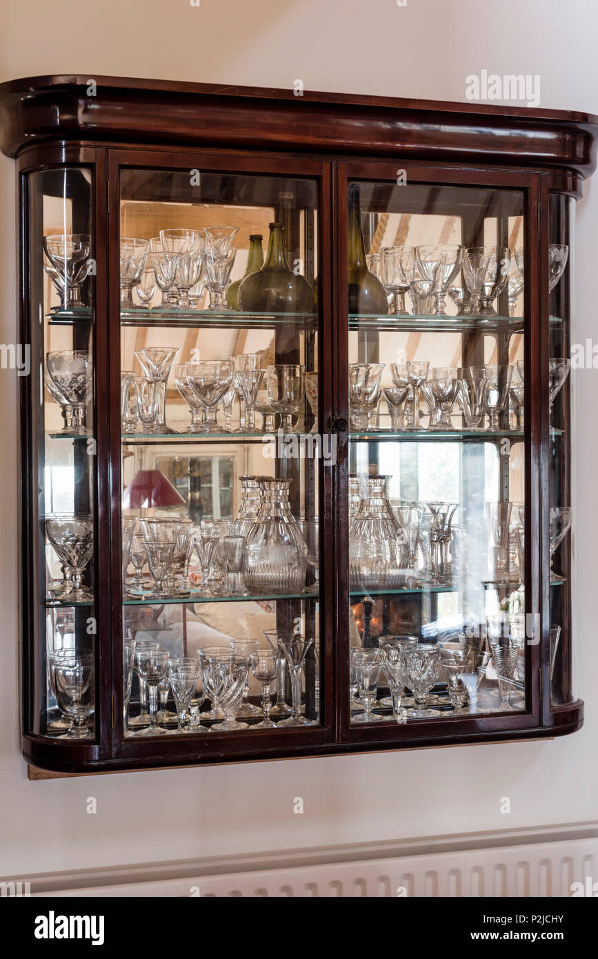 Early 20th century display cabinet with a collection of antique decanters and glasses, Sussex, UK - Stock Image