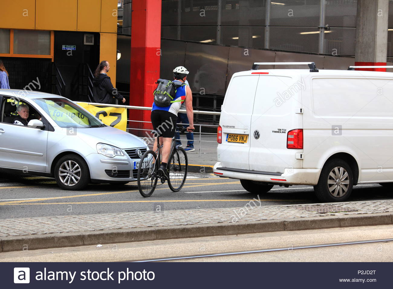 A Male cyclist weaves through moving traffic at Manchester City Centre, Manchester UK Summer June 2018 - Stock Image