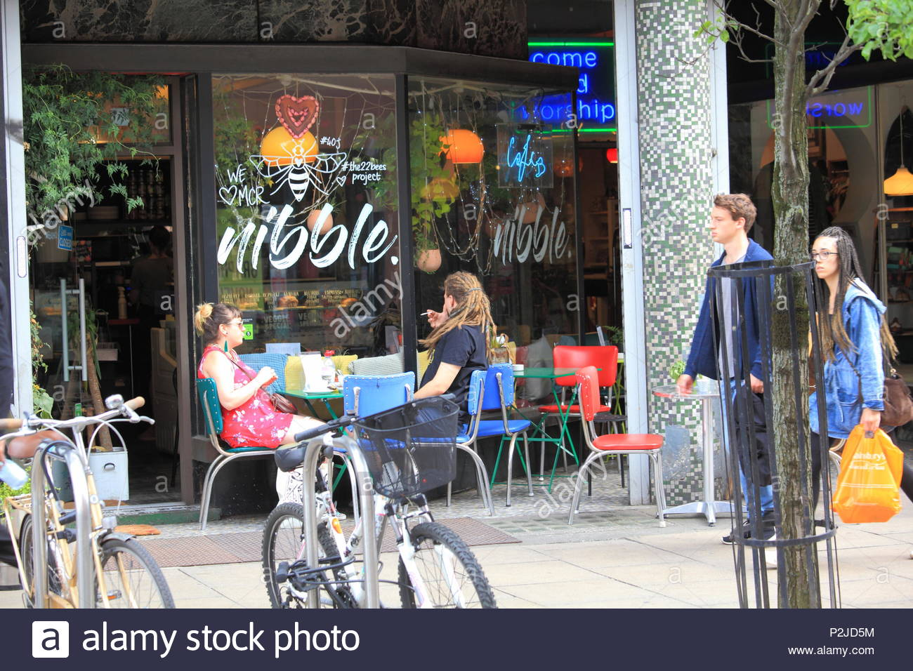 A Man With Dreadlock Hairstyle Sits Toking With His Girlfriend At Nibble Cafe Bar at Manchester City Centre, Manchester UK Summer June 2018 - Stock Image
