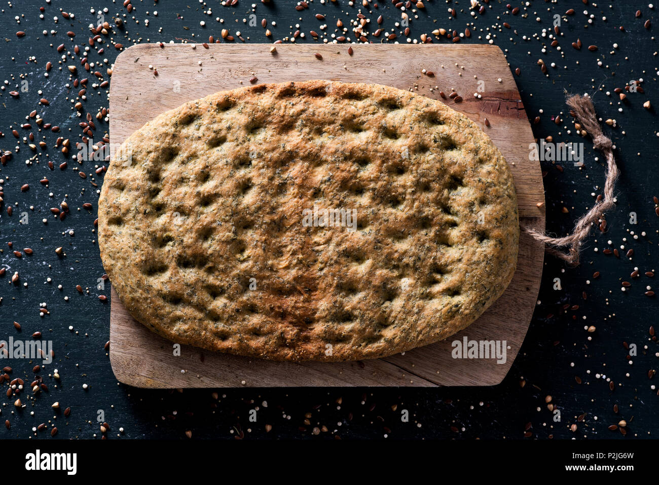 high angle view of a kale flatbread on a chopping board, placed on a dark green rustic wooden table - Stock Image