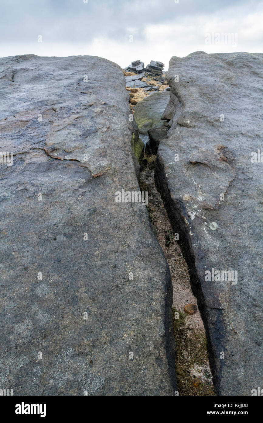 A fissure in gritstone rocks near Fairbrook Naze on Kinder Scout in Derbyshire, Peak District, England, UK - Stock Image