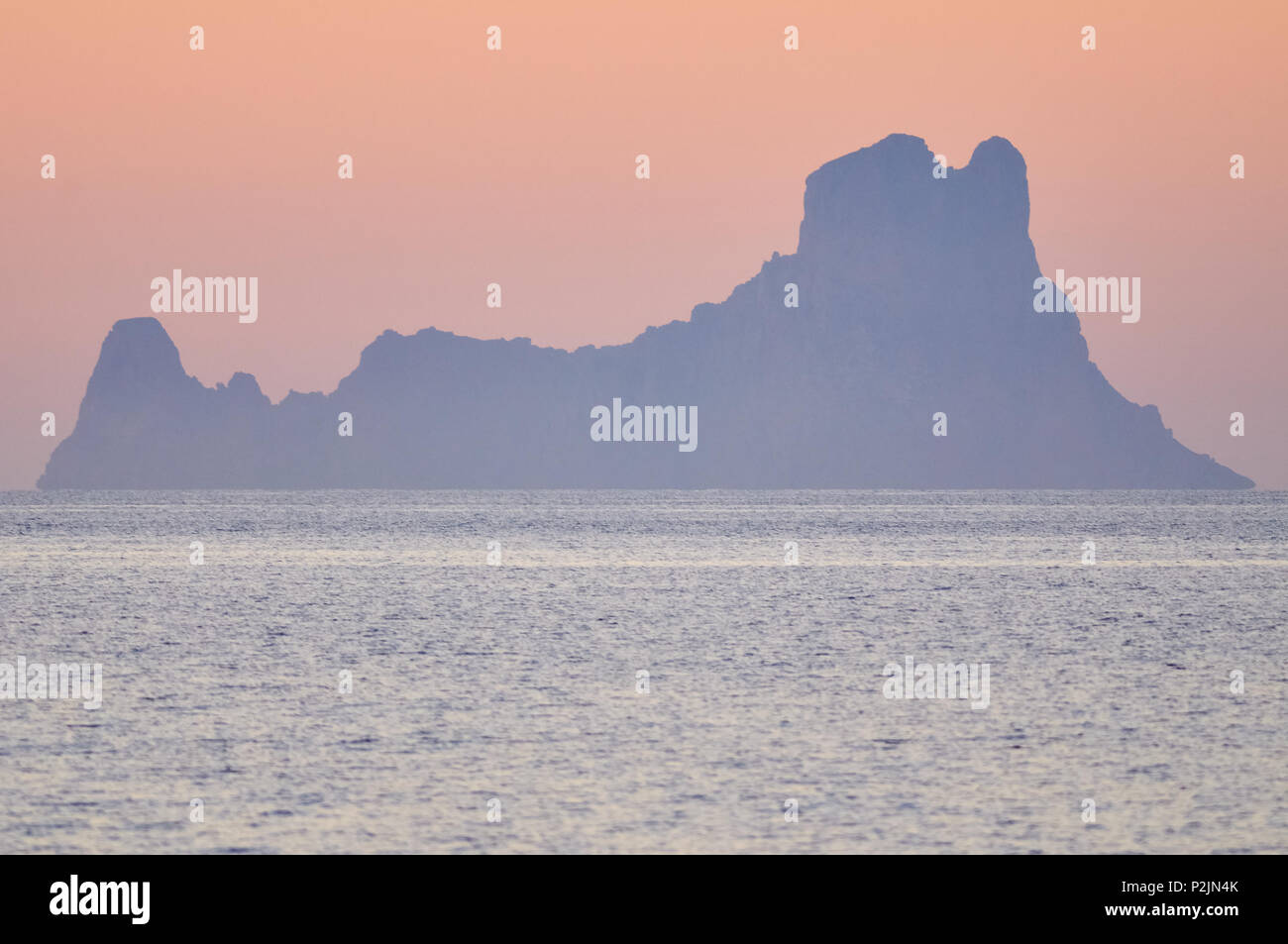 Panoramic view at sunset of Es Vedrá islet silhouette against red sky from Formentera (Pityusic Islands, Balearic Islands, Spain) - Stock Image