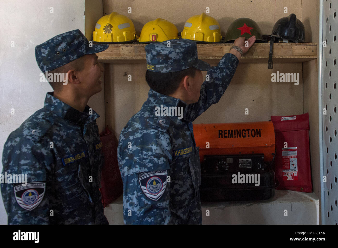 Two Mongolian emergency management cadets look at a Soviet Union helmet during a Disaster Management Leadership Seminar in Ulaanbaatar, Mongolia, Sept. 21, 2016. The five-day seminar is a subject matter expert exchange between the U.S. and Mongolia. The Mongolia National Emergency Management Agency hosted the exchange, partnering with U.S. service members from Special Operations Command, Pacific. The participants exchanged information on a variety of topics including disaster response management, human rights, displaced persons, incident command system, mass casualty incident management, crisi - Stock Image