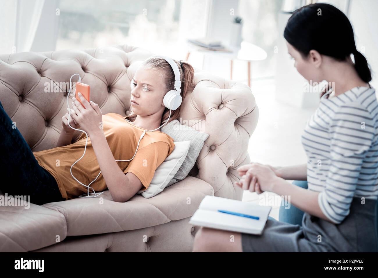 Upset girl listening to music during attending psychologist - Stock Image
