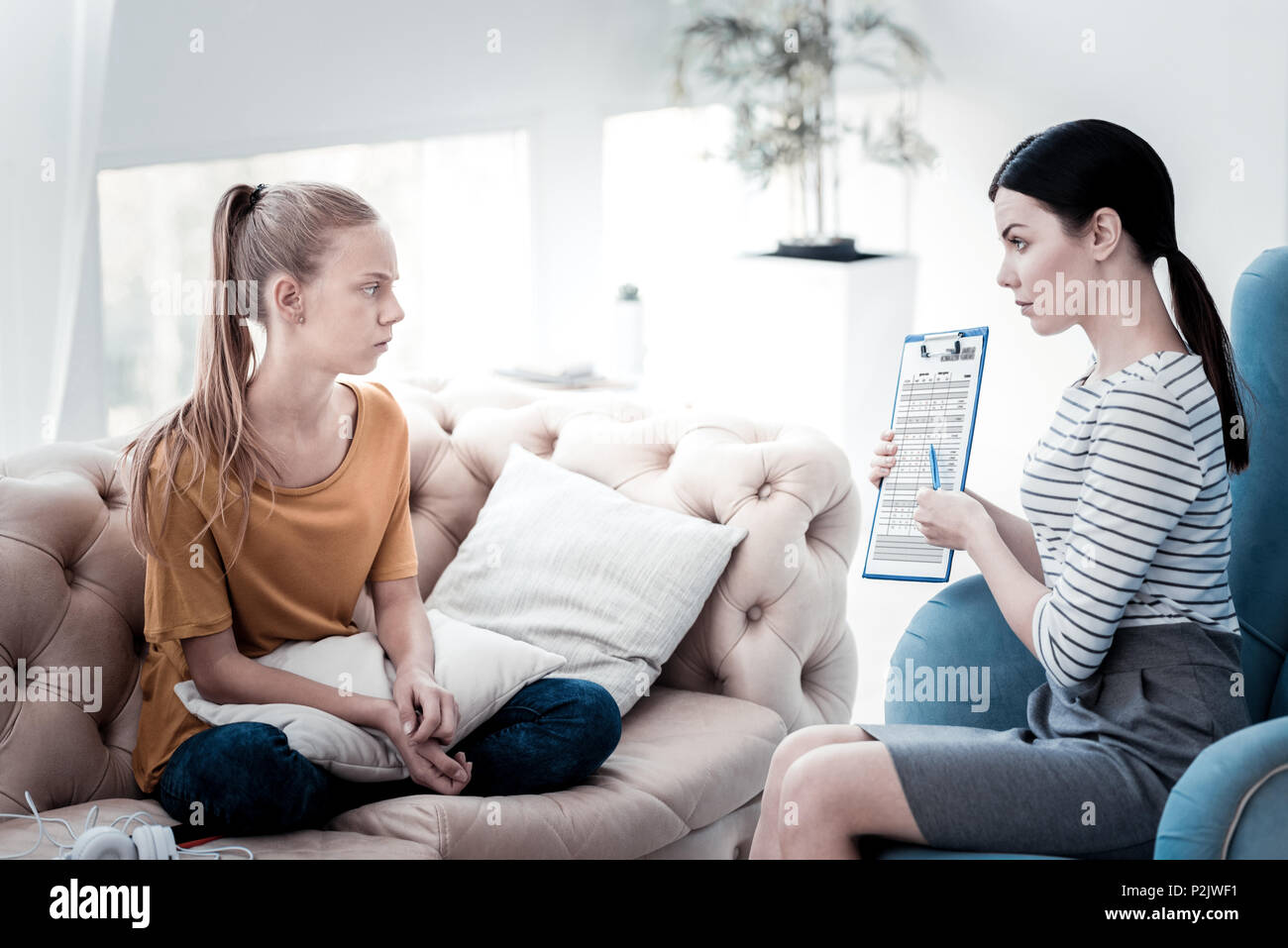 Confused girl looking at her test results presented by psychologist - Stock Image