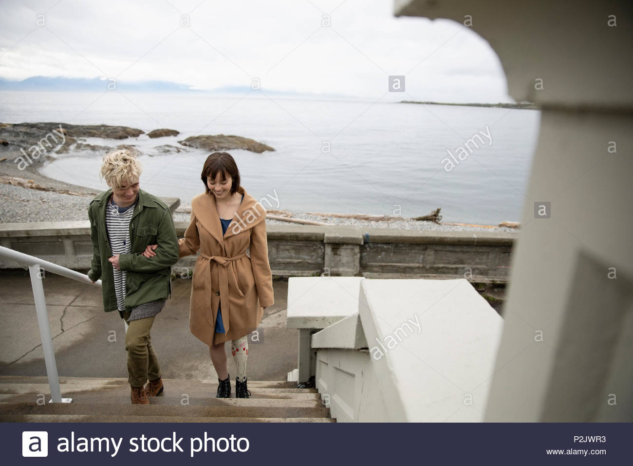 Young woman amputee walking with boyfriend up stairs overlooking beach - Stock Image