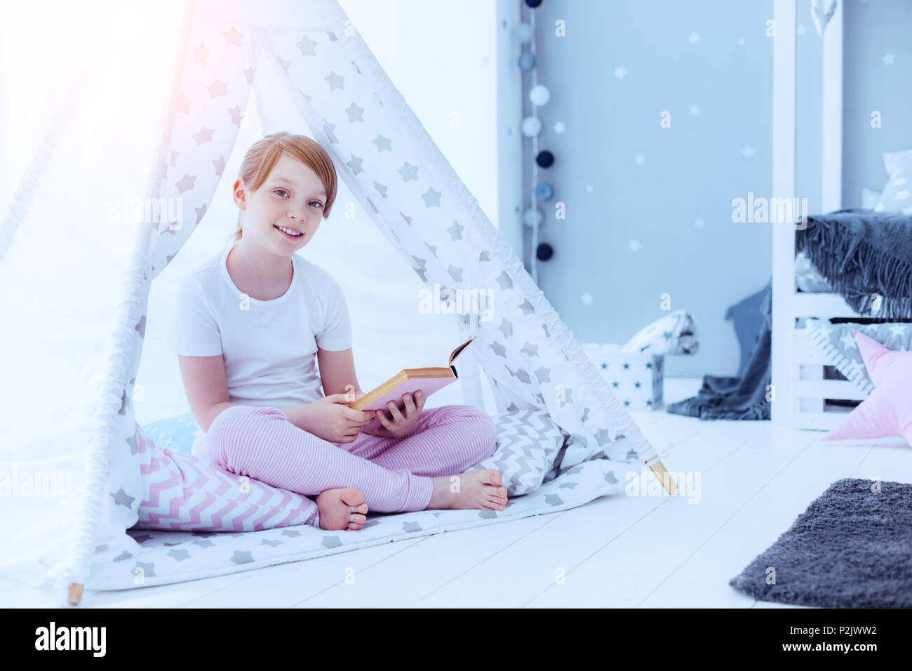 Pretty girl with book sitting in teepee at home - Stock Image