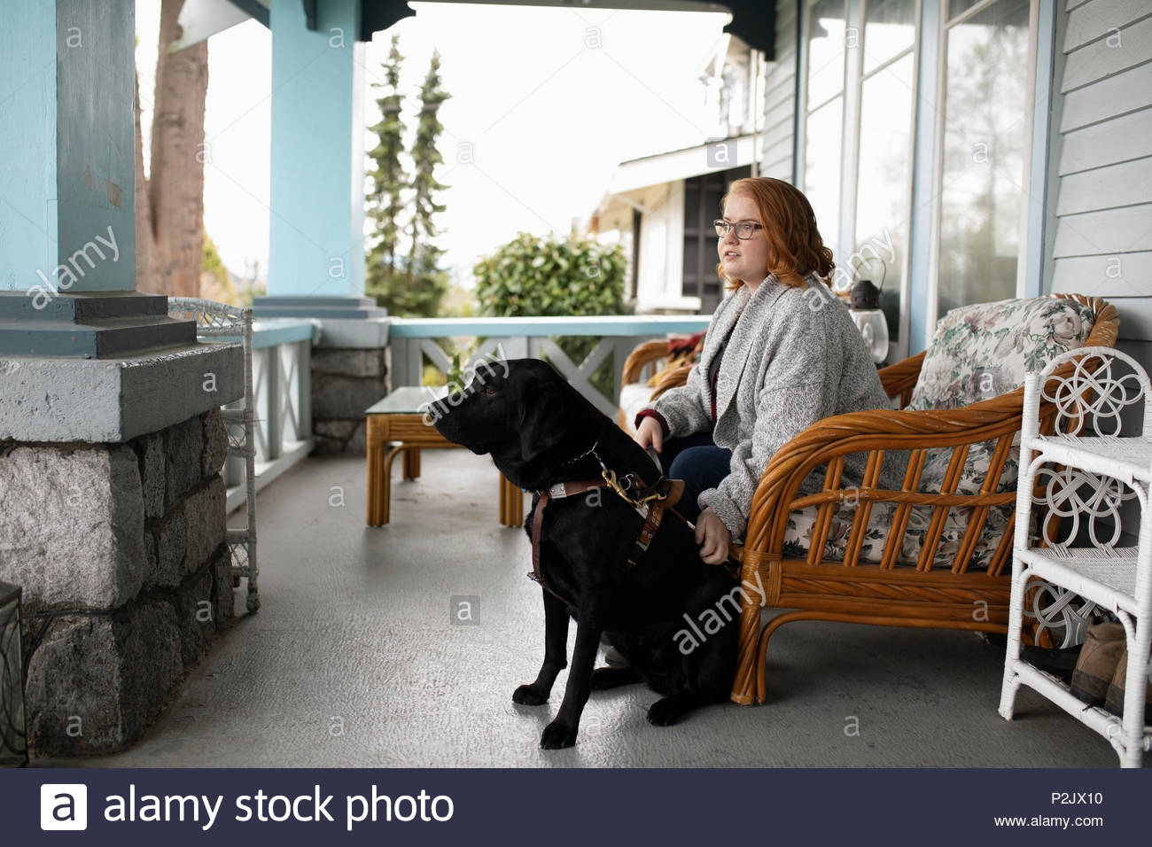 Visually impaired woman sitting with seeing eye dog on porch - Stock Image