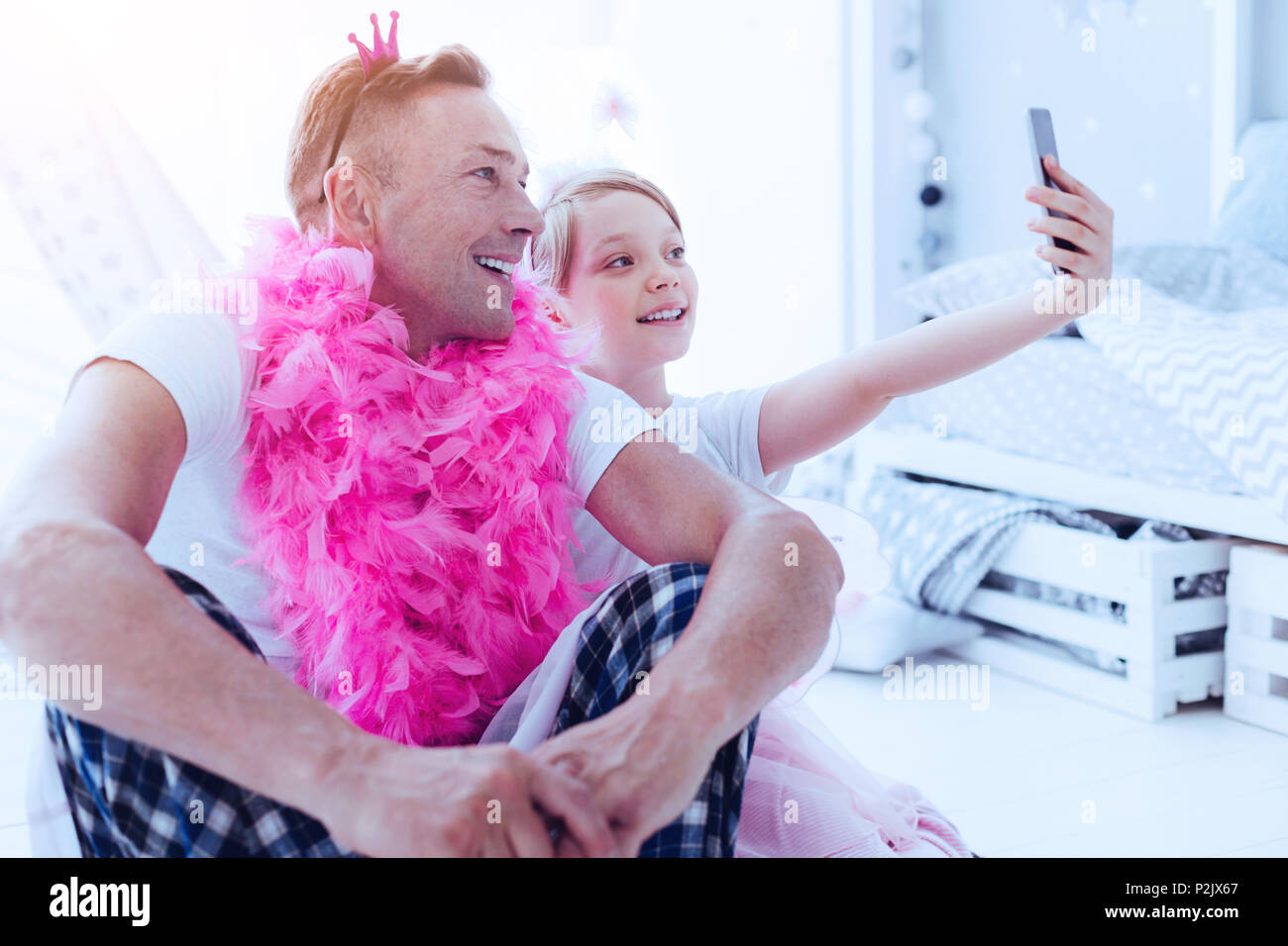 Adorable daughter and father taking selfie - Stock Image
