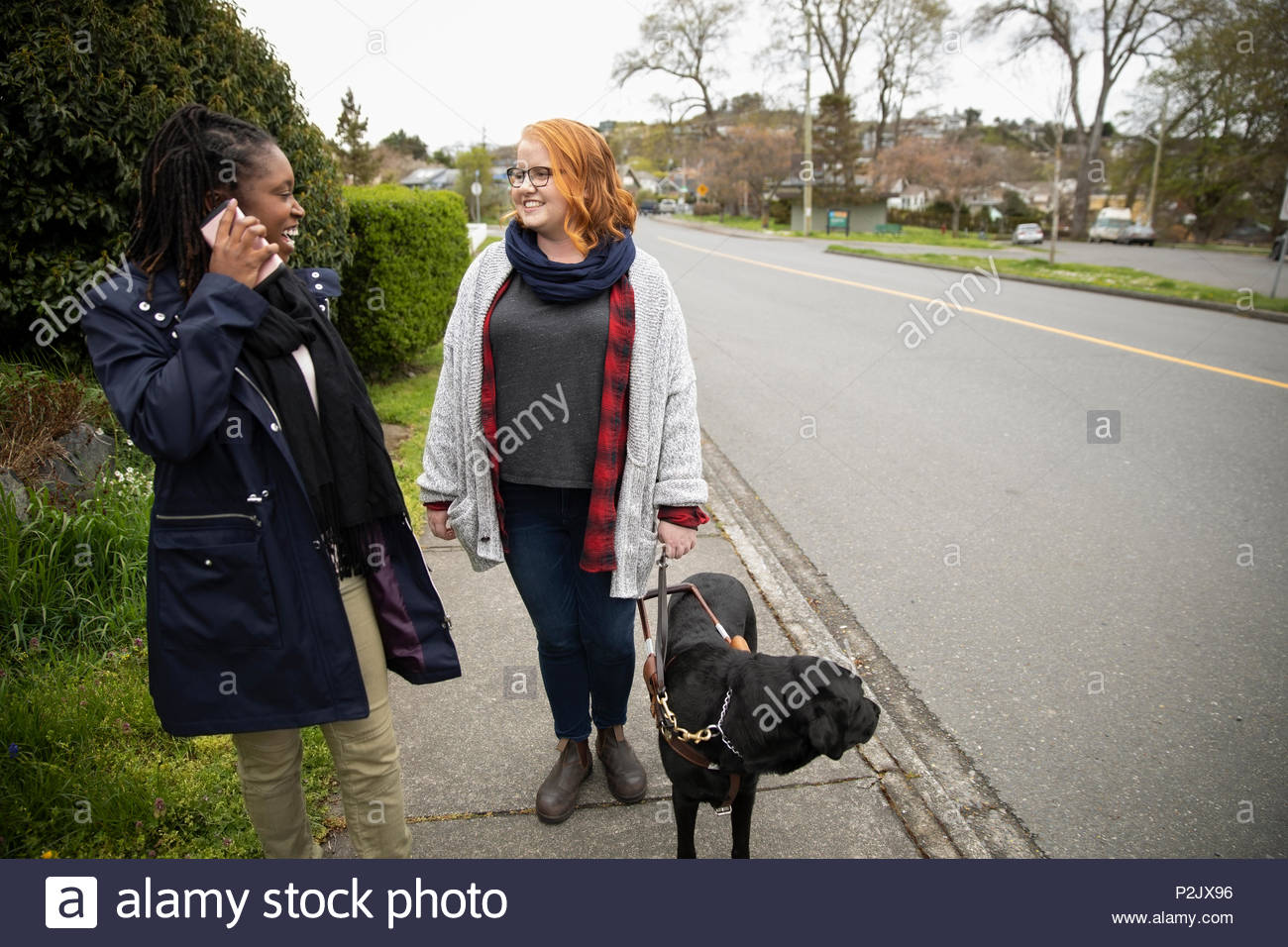 Visually impaired woman with seeing eye dog talking with friend on sidewalk - Stock Image