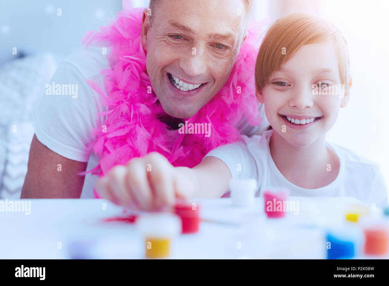 Radiant family members painting and having fun - Stock Image