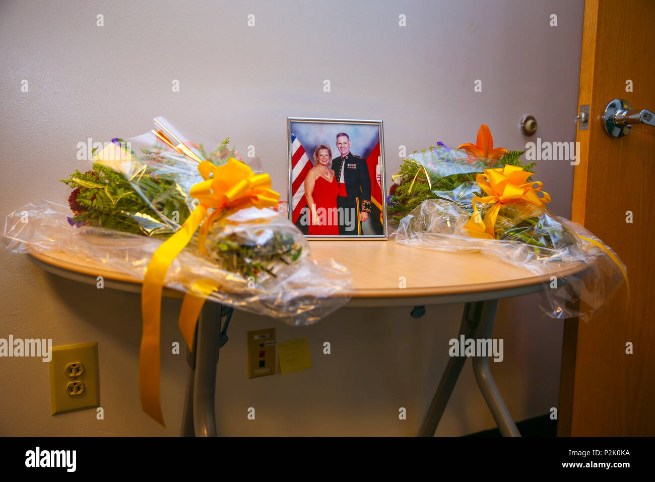 A picture of Mrs. Marla Rankin and Edward Gillis, husband, is displayed with a bouquet of flowers at the beginning of Mrs. Rankin's retirement ceremony, on Marine Corps Base Quantico, Va., Sept. 29, 2016. Rankin served 32 honorable years of civilian service. (U.S. Marine Corps photo by Lance Cpl. Cristian L. Ricardo) - Stock Image