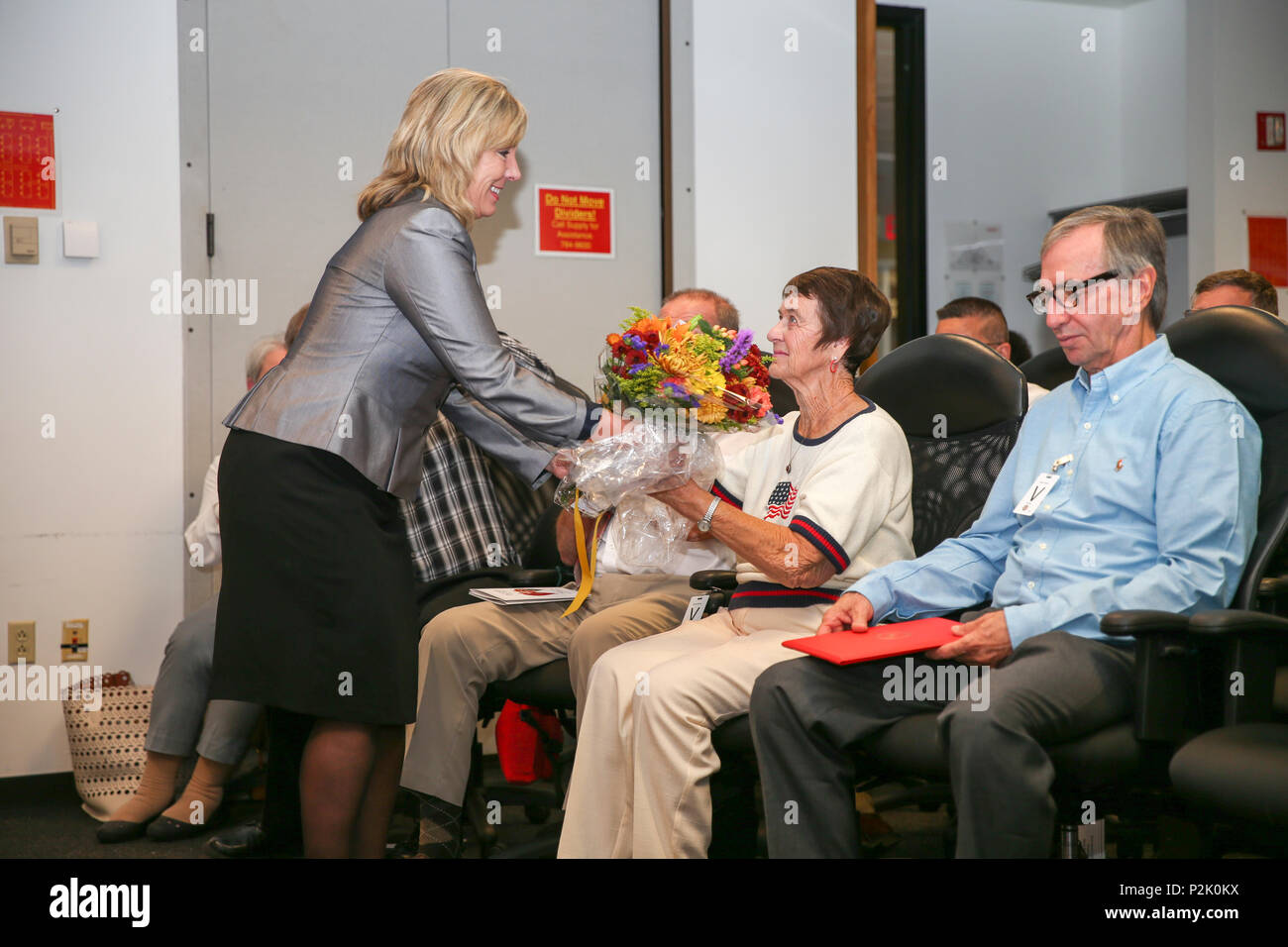 Ms. Kelly F. Sims gives a bouquet of flowers to a family member of Mrs. Marla Rankin during Rankin's retirement on Marine Corps Base Quantico, Va., Sept. 29, 2016. Rankin served 32 honorable years of civilian service. (U.S. Marine Corps photo by Lance Cpl. Cristian L. Ricardo) - Stock Image