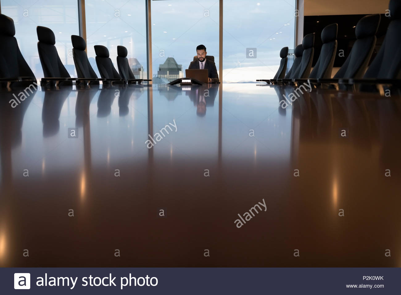 Dedicated businessman working late in boardroom - Stock Image