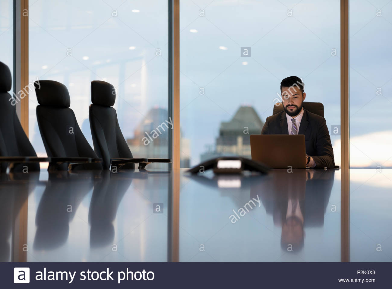 Dedicated businessman working late at laptop in boardroom - Stock Image