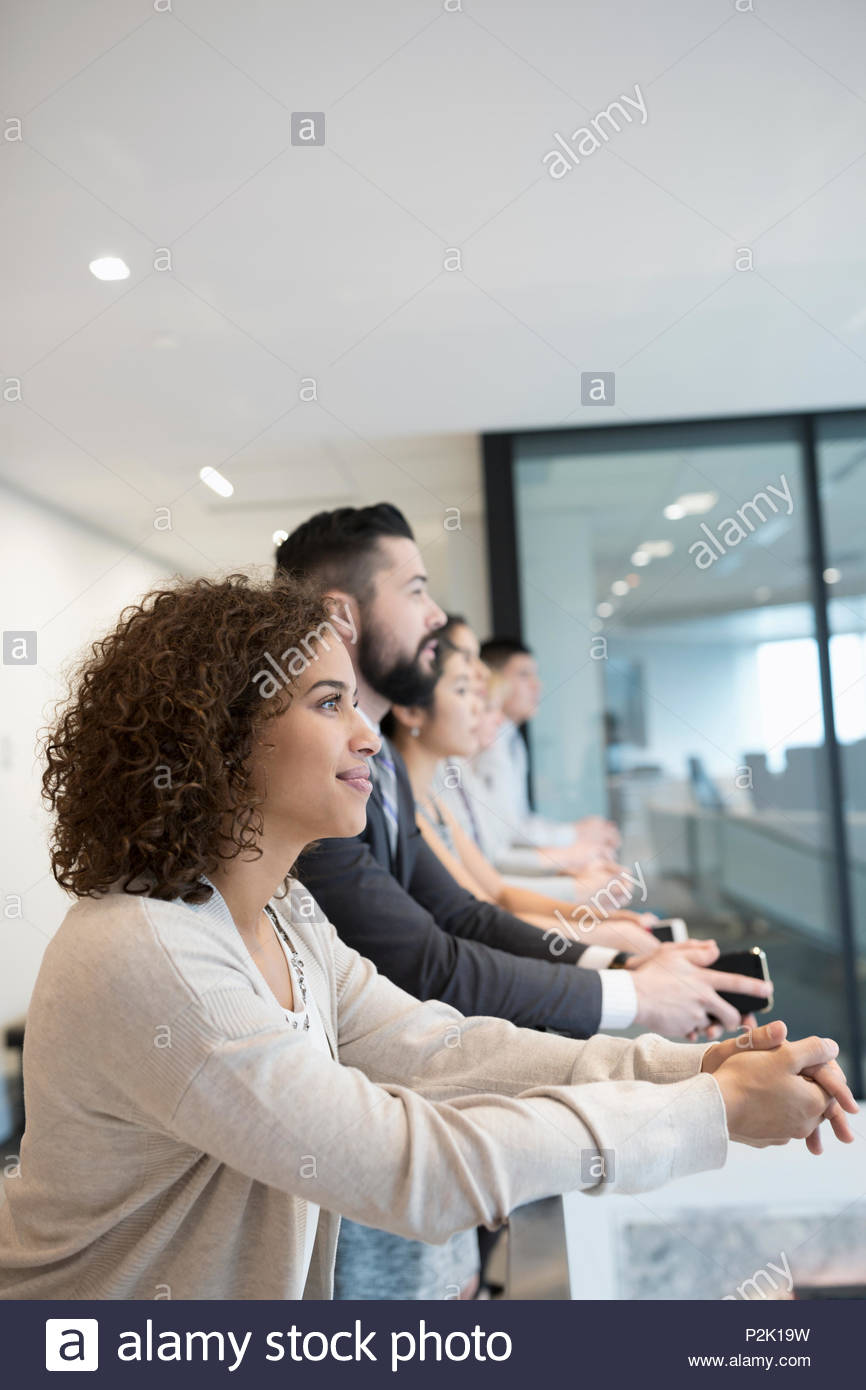 Forward looking, ambitious business people at office railing - Stock Image