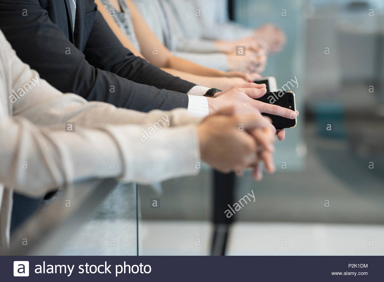 Close up business people with smart phones at railing - Stock Image