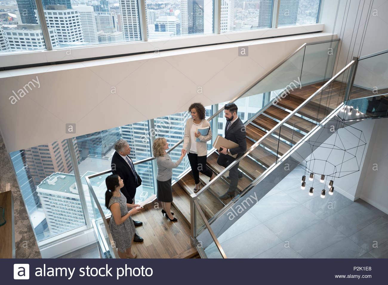 Business people handshaking on modern, urban office staircase Stock Photo