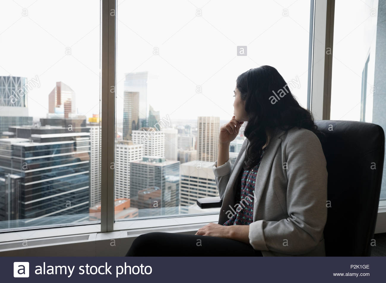 Forward looking businesswoman looking out urban office window - Stock Image