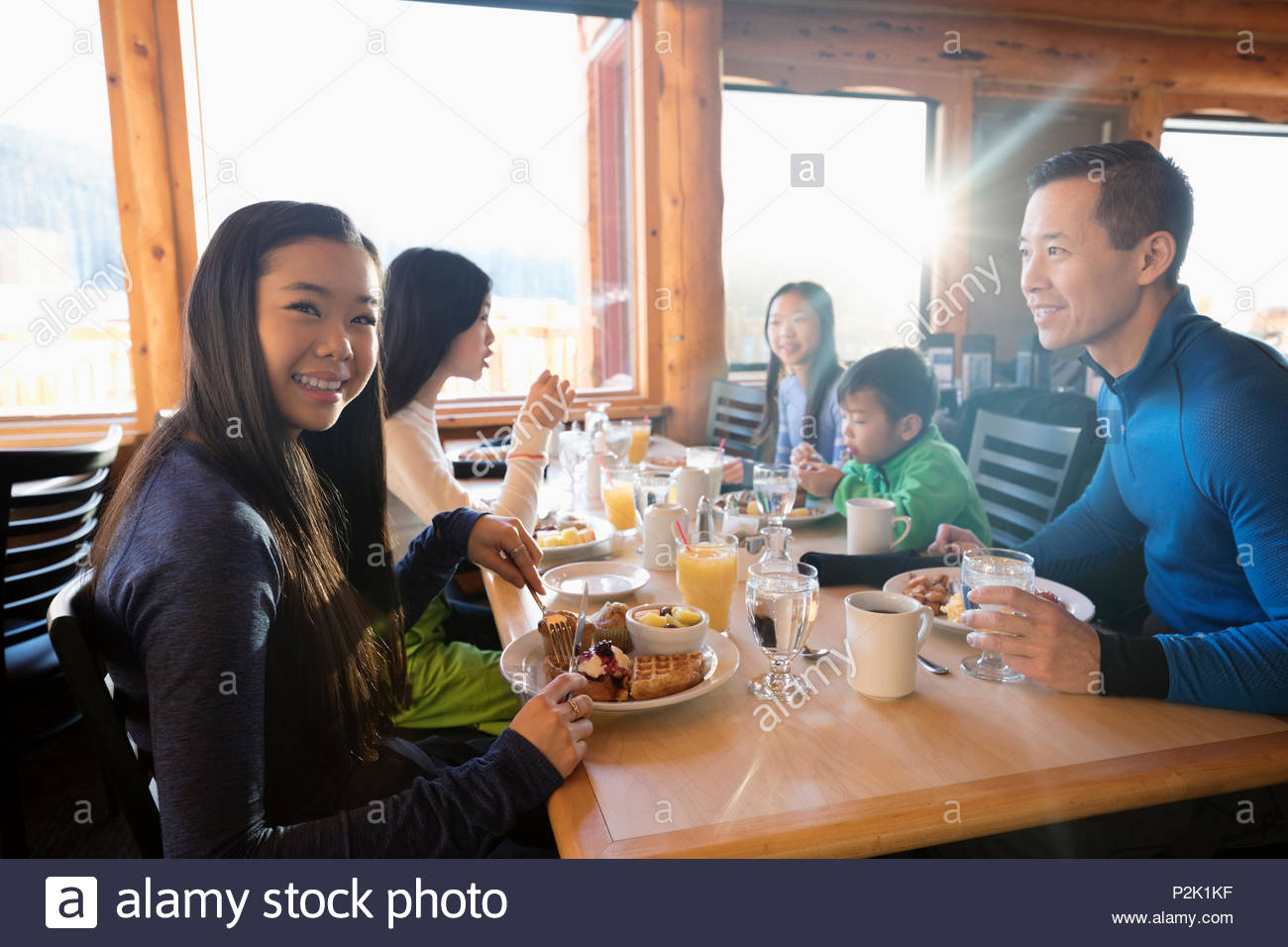 Portrait confident teenage girl enjoying breakfast with family at cabin table - Stock Image