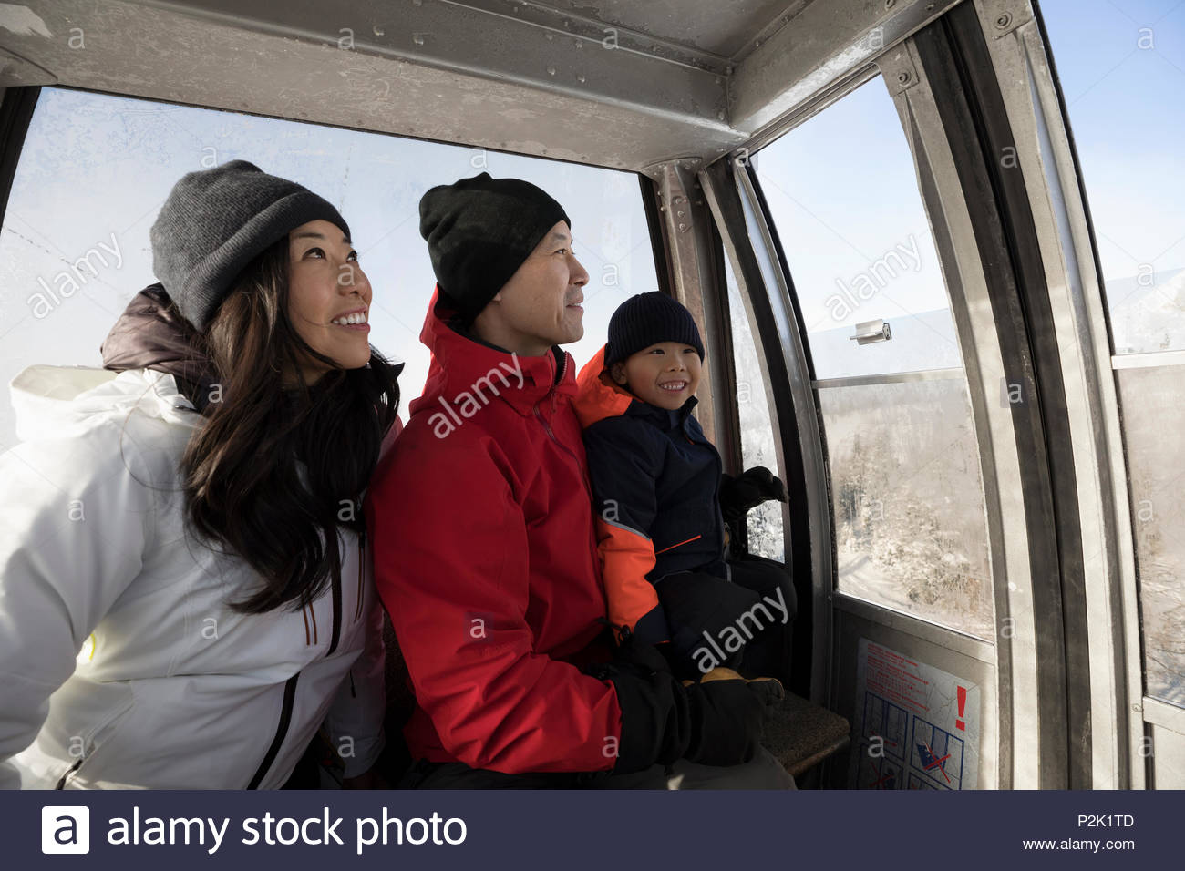 Family skiers riding gondola - Stock Image