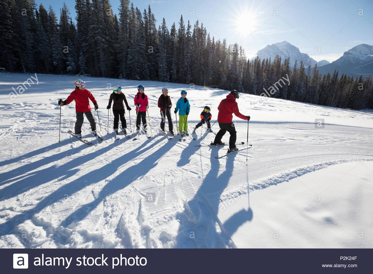 Family receiving group ski lesson from ski resort instructor - Stock Image