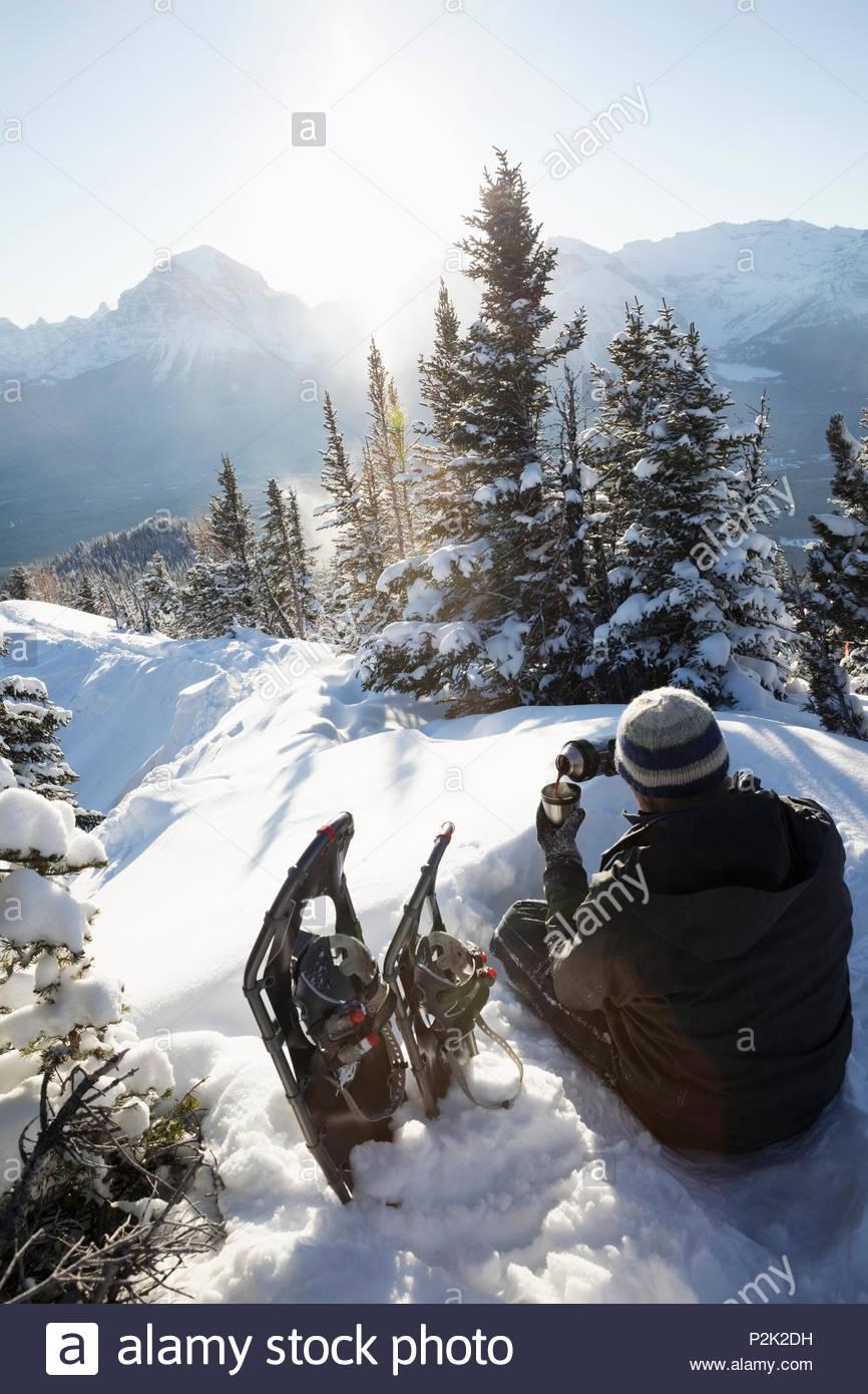 Solo traveler snowshoer taking a break, drinking coffee on sunny, idyllic mountain - Stock Image